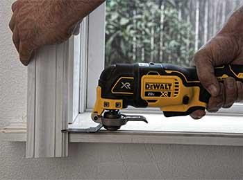 multifunciones eléctrica oscilatoria marca Dewalt haciendo corte en ventana